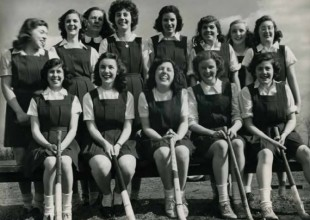 Photo: 1943: Teammates pose in their brown wool tunics with coach Mott Hunt.