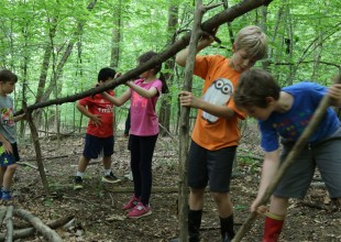 Photo: Third graders venture into the woods on campus to create survival tools and shelters, providing the context to explore the ways in which environments, values, and colonization shape how cultures meet their basic needs.
