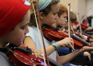 Photo: In 4th Grade, students have an exploratory music class once a week, giving them a chance to work with a variety of instruments (strings, brass, and winds) before choosing their ensemble class in 5th Grade.